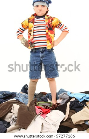 Adorable seven year old boy playing with pile of laundry.  Wearing mismatched clothes and underwear on his head. - stock photo