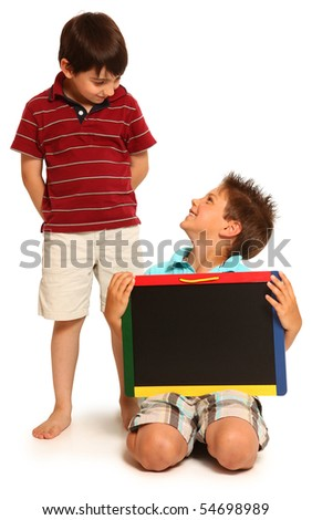 adorable seven year old boys holding blank chalk board