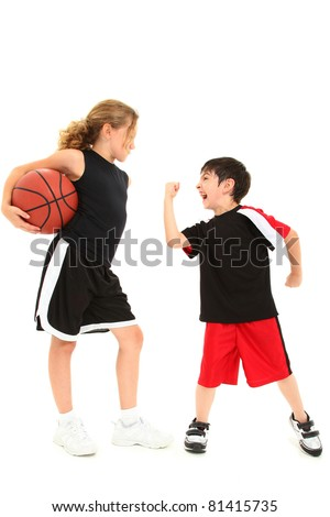 Adorable short boy child shaking fist at taller girl basketball player over white. - stock photo