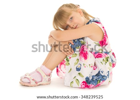 Adorable, shy little girl with short blonde bangs sitting on the floor in a pink summer dress with short sleeves. The girl thoughtfully sitting on the floor with his arms around his legs and his head - stock photo