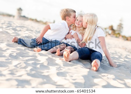 Adorable Sibling Children Kissing the Youngest Girl at the Beach. - stock photo