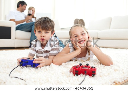 Adorable siblings playing video games lying on the floor - stock photo