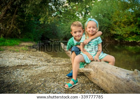 Adorable siblings posing for a portrait, summer outdoors concept - stock photo
