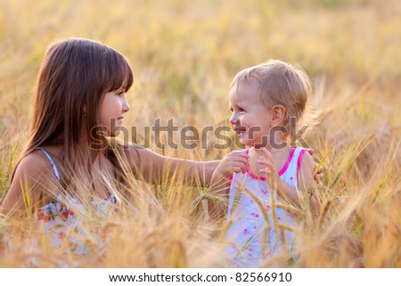 adorable sisters in the field of wheat - stock photo