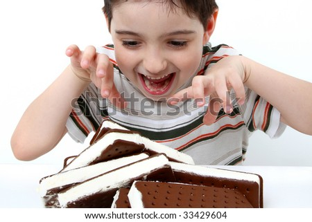 Adorable six year old boy attacking a pile of ice cream sandwiches.