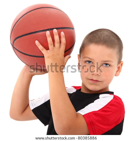Adorable six year old boy child with basketball in uniform over white background.