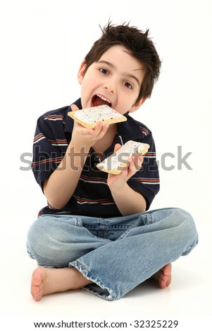 Adorable six year old boy laughing and eating pop tarts.  Sitting on white floor. - stock photo