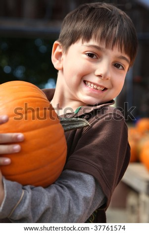 Adorable six year old caucasian boy picking pumpkin at farm.