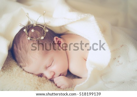 adorable sleeping baby princess with golden crown, newborn photography, soft focus