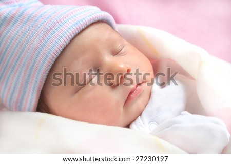 Adorable sleeping new born baby all bundled up in blankets.