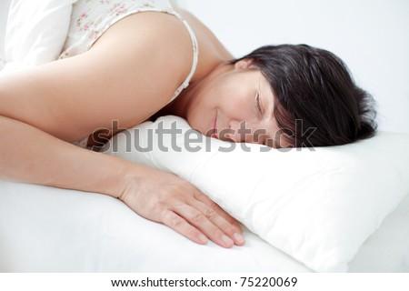 Adorable sleeping smiling woman - stock photo