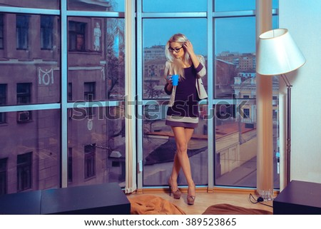 Adorable slim blonde woman with cup of tea by the large window with city views . Business woman drinks tea. City views behind the window in the office. Business concept. - stock photo