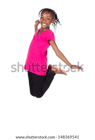 Adorable small african child with braids wearing a bright green shirt and black skinny jeans. The girl is jumping and smiling.