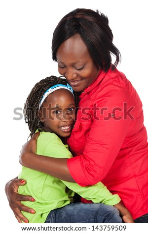 Adorable small african child with braids wearing a bright green shirt and blue jeans and her mother wearing a red shirt. The mom is holding and hugging the girl.
