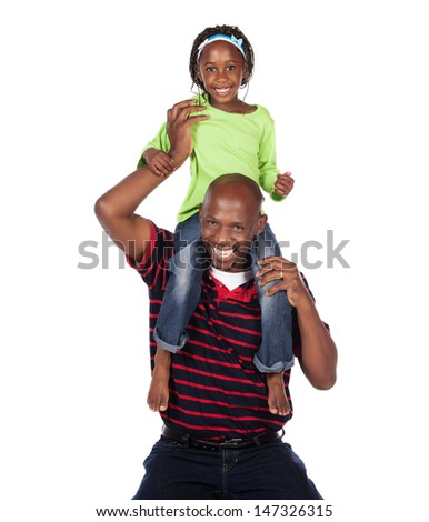 Adorable small african child with braids wearing a bright green shirt and blue jeans is playing with her father. He is wearing a red striped shirt.