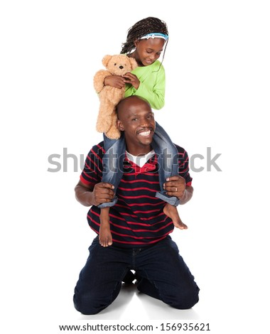 Adorable small african child with braids wearing a bright green shirt and blue jeans is playing with her father. He is wearing a red striped shirt. She is holding a teddy bear. - stock photo
