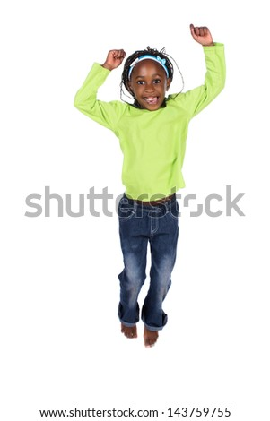 Adorable small african child with braids wearing a bright green shirt and blue jeans. The girl is jumping and smiling. - stock photo