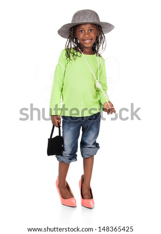 Adorable small african child with braids wearing a bright green shirt and blue jeans. The girl is playing dress up with a hat and high heels. - stock photo