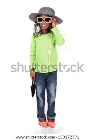 Adorable small african child with braids wearing a bright green shirt and blue jeans. The girl is playing dress up with a hat sunglasses and high heels. - stock photo