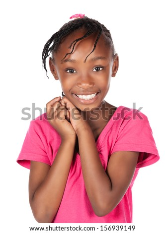 Adorable small african child with braids wearing a bright pink shirt. The girl is standing and smiling at the camera. - stock photo