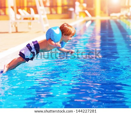 Adorable small boy jumping to the pool, having fun in aquapark, happy summer holidays, day care, active lifestyle, luxury tropical resort  - stock photo