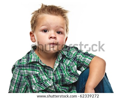 Adorable small boy looking at the viewer in a pensive mood. - stock photo