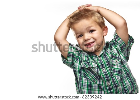 Adorable small boy smiling and wearing plaid with his hands on his head. - stock photo