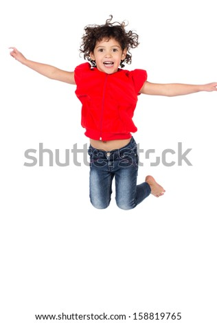 Adorable small caucasian child with curly hair wearing a bright red hooded top and blue jeans. The girl is jumping and smiling. - stock photo
