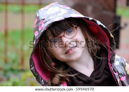 Adorable small girl in  glasses in hood of colorful rain coat looking into  the camera