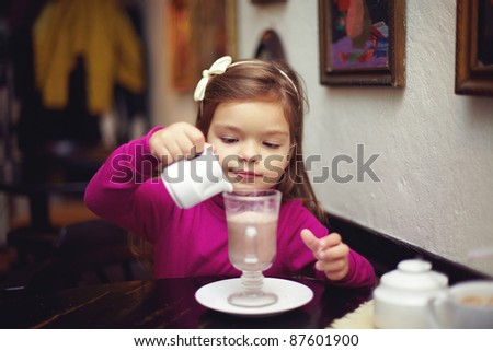 adorable small girl pouring cream into cappuccino. indoor cafe - stock photo