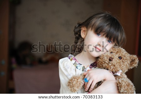Adorable small girl with dark hair in grey dress hugs her toy bear - stock photo