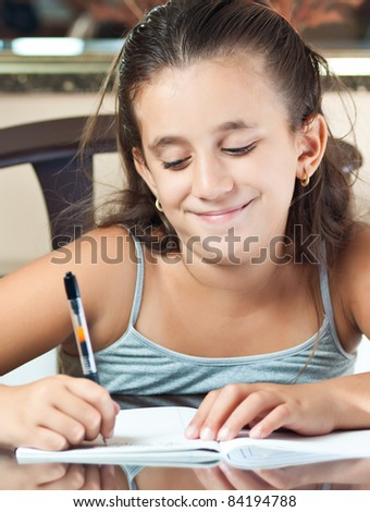 Adorable small latin girl working on her school project at home - stock photo