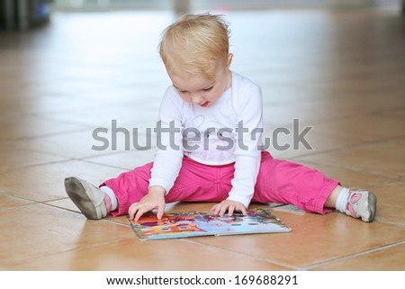 Adorable smart little baby or toddler girl reading book sitting indoors on a tiles floor - stock photo