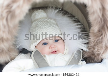 Adorable smiling baby girl in a warm stroller wearing a winter snow jacket and a hat on a walk in a cold park - stock photo