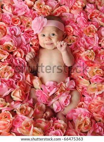 Adorable smiling baby girl lying in a bed of pink roses - stock photo