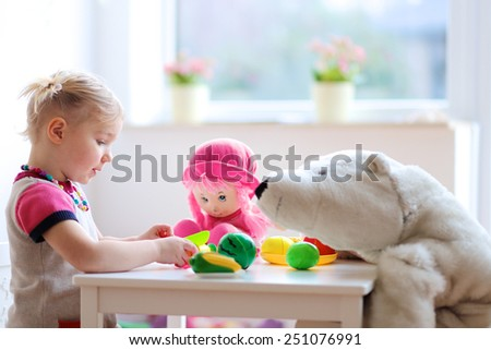 Adorable smiling child, blonde toddler girl, playing at home or kindergarten, cutting plastic vegetables with knife and feeding her toys, a doll and a teddy bear. Promoting healthy lifestyle for kids. - stock photo