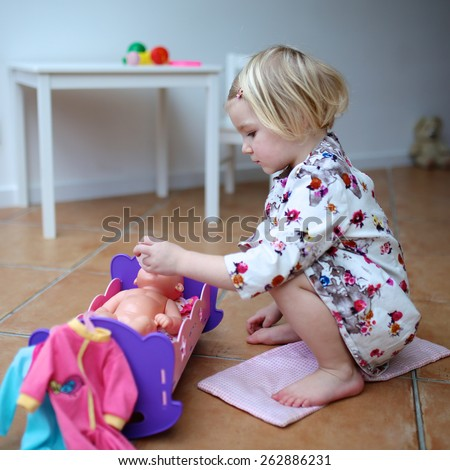 Adorable smiling child, blonde toddler girl wearing beautiful dress, playing at home or kindergarten, feeding her doll with toy bottle, sitting on warm tile floor