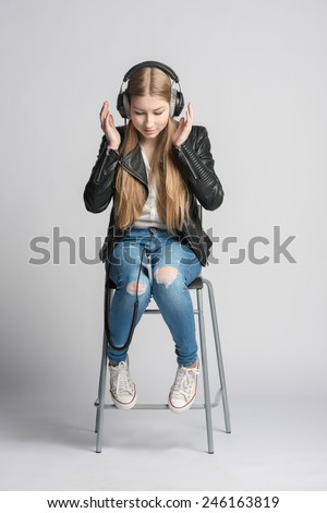 Adorable smiling girl in wired headphones is sitting and listening music from her own smartphone - stock photo
