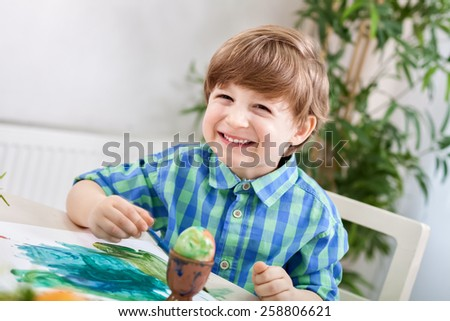 Adorable smiling happy child boy painting on paper and egg - stock photo