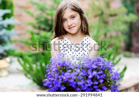 Adorable smiling kid girl in elegant dress holding flowers in the garden - stock photo