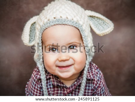 Adorable smiling kid in sheep hat - stock photo
