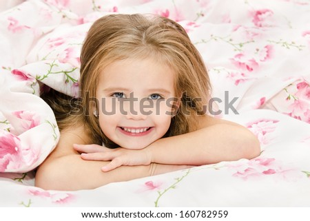 Adorable smiling little girl awaked up in her bed  - stock photo