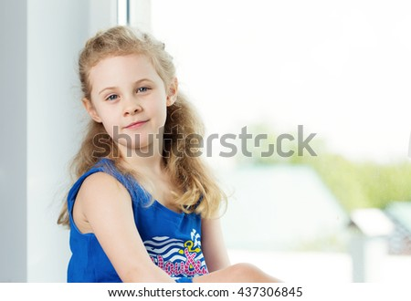 Adorable smiling little girl by the window - stock photo