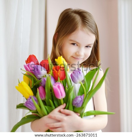 Adorable smiling little girl holding tulips by the window - stock photo