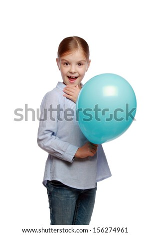 Adorable smiling little girl in casual clothes holding a blue air balloon and having fun on white background on Holiday