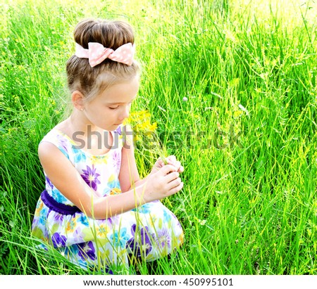 Adorable smiling little girl on the meadow smelling the flowers in summer day outdoor