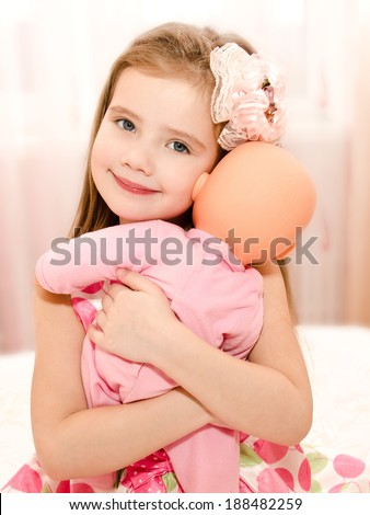 Adorable smiling little girl playing with a doll at home - stock photo