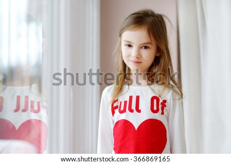 Adorable smiling little girl wearing funny tshirt by the window - stock photo