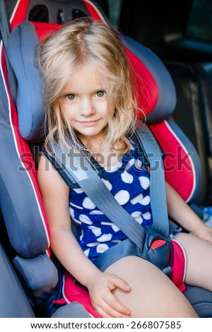 Adorable smiling little girl with long blond hair buckled in car seat looking through the car window - stock photo