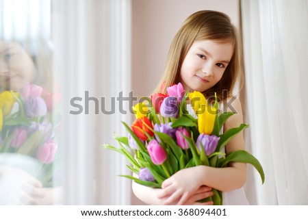 Adorable smiling little girl with tulips by the window - stock photo